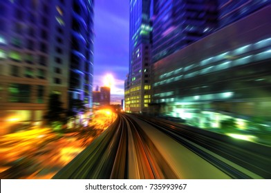 High speed train passing in between Kuala Lumpur City during dusk hour.