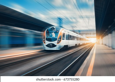 High speed train at the railway station at sunset in Europe. Modern intercity train on railway platform. Urban scene with beautiful passenger train on railroad and buildings. Railway landscape