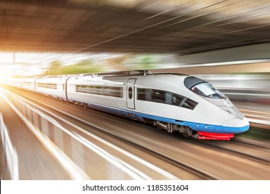 High speed train rides at high speed at the railway station in the city, through a tunnel under a bridge