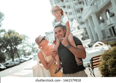 High spirits. Cheerful little girl riding her smiling fathers shoulders with her mother standing behind her.