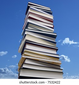 high stack of books in front of a blue sky