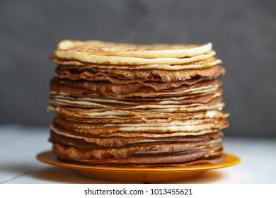 High stack of classic Russian thin pancakes. Rustic style. Traditional for the Russian pancake week (Maslenitsa)