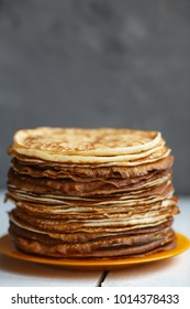 High stack of classic Russian thin pancakes. Rustic style. Traditional for the Russian pancake week Maslenitsa .