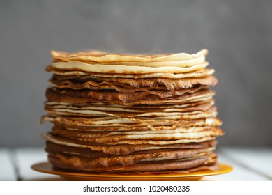 High stack of classic Russian thin pancakes with red currant. Rustic style. Traditional for the Russian pancake week Maslenitsa.