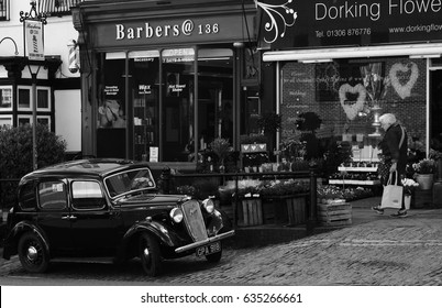High Street, Dorking, Surrey, United Kingdom, 25 April, 2017: An Austin Ruby Car Parked Outside a Flower and Barber Shop with an Elderly Person Walking By.
