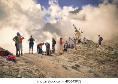 HIGH TATRA MOUNTAINS - SEPTEMBER 15, 2016: Tourists on mountain pass admiring views in High Tatra, Slovakia.