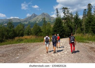 High Tatras, Slovakia - August 18, 2017: Young men walking along a mountain path in High Tatras in Slovakia