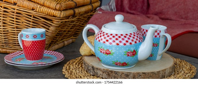 High tea picnic concept with decorated tea pot, teacups and picnic basket on a table