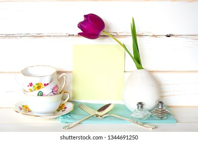 High Tea Time with Stack of Colorful Teacups, Purple Tulip in Vase, fork and spoon, with light green menu card on White Wood Board background and table.  A horizontal with side view