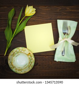 High Tea Time Table Place Setting with Vintage Cup and Saucer, yellow tulip, silverware, napkin and blank menu card with room or space for copy, text, or words.