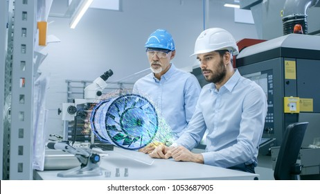In High Tech Factory Two Engineers Works with Holographic Projection 3D Model of the Engine Turbine Prototype. Futuristic Desing of Virtual Mixed Reality Application.