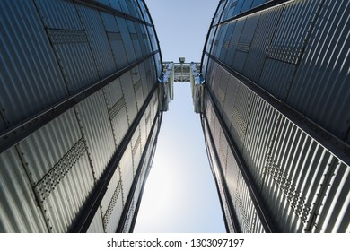High tech glass and concrete buildings of modern plant for storage and processing crops. Big granaries in sunny summer day minimalist style copyspace