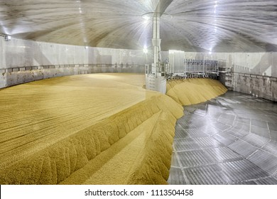 A high tech stailnless steel drying kiln in a clean, modern barley malting facility, being filled with layers of sprouted barley.