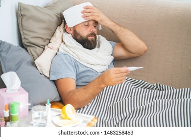 High temperature concept. Man feels badly ill. How to bring fever down. Cold symptoms and causes. Sick man with flu. Man hold thermometer. Measure temperature. Break fever remedies.