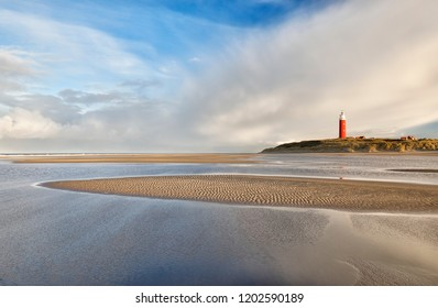 high tide on sand beach by red lighthouse
