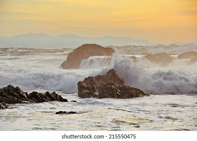 High tide at sunset crashing on shore line rocks near Botanical Beach, Port Renfrew, Vancouver Island, British Columbia in the Strait of Juan de Fuca, Pacific Ocean, across from the Olympic Mountains.
