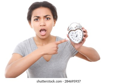 High time. Emotional young pretty woman pointing on alarm clock on white isolated background.
