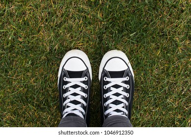 High top black and white sneakers on the grass