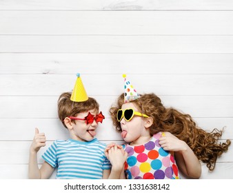 High top view with happy children on carnival party, lying on a wooden floor. Happy childhood, Holiday concept.