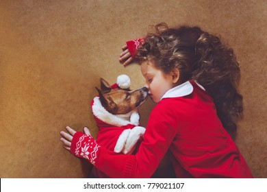 High top view with little friend. Santa girl embracing puppy dog. Christmas, New year holiday concept.