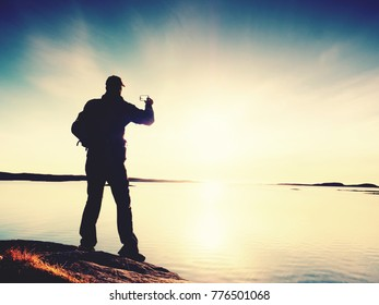 High tourist  taking selfie on mobile phone against scenic view of sea against evening sky. Sun mirror in smooth water level. Silent sea bay