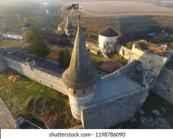 High tower of ancient mighty fortress in Kamianets-Podilskyi, Western Ukraine. Medieval castle in Kamianets-Podilskyi, Ukraine, aerial autumn morning view. Weathercock on roof, loopholes on turret.