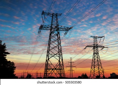 high tower electrical lines are silhouette on beautiful sunset