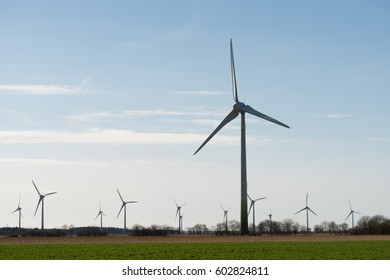 High turbine tower or windmill standing on the field with a number of windmills on background