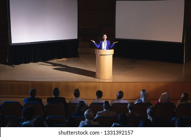 High view of beautiful businesswoman standing around podium and giving presentation to the audience in auditorium
