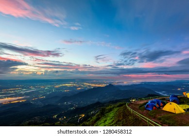 High view beautiful nature landscape of colorful sky during the sunrise, see the lights of the road and city from the campsite at Phu Thap Berk viewpoint, Phetchabun Province, Thailand