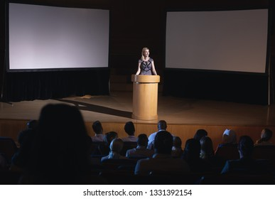 High view of blonde Caucasian businesswoman standing around podium and giving presentation to the audience in auditorium