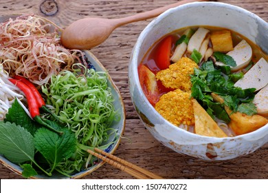 High view bowl of homemade vegan rieu noodle soup or vegetarian crab paste vermicelli soup, a traditional Vietnamese dish, plate of vegetables, herbs, ready to eat