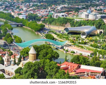 High view Day time scenery of Tbilisi downtown , Bridge of Peace, Kura river, church and building in capital city of Georgia.