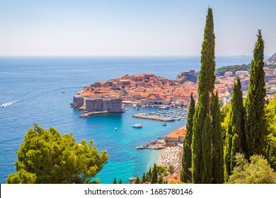 A high view of Dubrovnik Old Town showing the outside of buildings, boats and the sea.