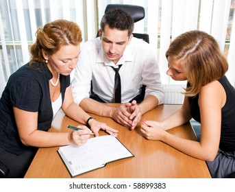 High view of handsome manager man speaking with his office workers during meeting in board room. Red-haired lady demonstrating her opinion about new strategy.