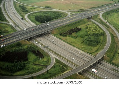 High view from plane on green scenery with beautiful round crossroads and bridges with cars driving on road onnatural background, horizontal picture