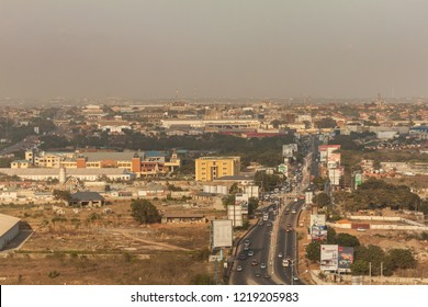 High view point cityscape of Accra, Ghana. Traffic on Spintex Road going East with billboards, constructions sites, wasteland and business buildings and hazy horizon