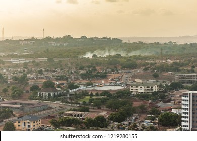 High view point cityscape of a neighborhood  in de hills of Accra, Ghana. Apartment buildings, slums, construction sites, wastelands and streets . Smoke from burning waste with a green and hazy horizo