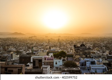 High view showing part of the Udaipur skyline at sunrise. Lots of buildings can be seen and hills and the sun can be seen in the distant.