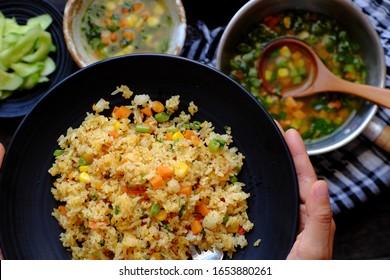 Femme à la vue élevée préparer à la main la nourriture pour un dîner rapide, un repas végétarien avec du riz pilaw frit à la soupe de légumes comme de la carotte, du maïs, des haricots à cordes, un plat végétarien en jaune, une délicieuse cuisine vietnamienne
