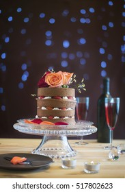 High vintage naked chocolate cake with fresh strawberry on glass cake stand on moody background with light bulbs.