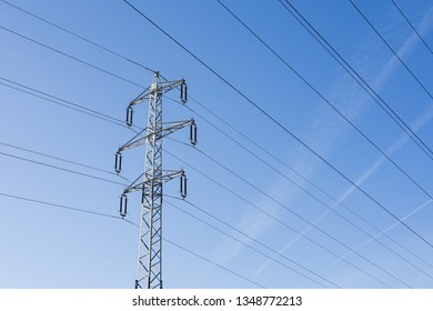 High voltage columns, in the background with blue sky and clouds. Prices of electricity, consumption, ecology.