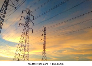 High voltage electric pole with sky and clouds and the sunlight in the evening silhouette.
