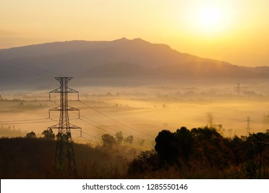 High voltage electric power transmission tower on hills along the valley with misty morning