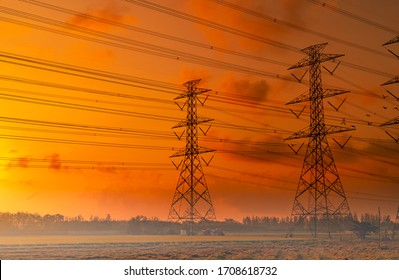 High voltage electric pylon and electrical wire with sunset sky. Electricity poles. Power and energy concept. High voltage grid tower with wire cable. Beautiful red-orange sunset sky. Infrastructure.