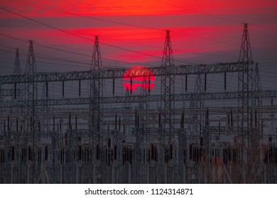 High Voltage electric substation with transformers at sunset