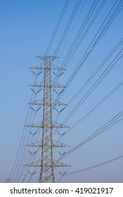High voltage electric tower on blue sky.