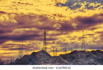 High voltage electric tower at sunset. Storm clouds in the sky.