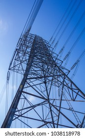 High voltage electric transmission power line towers with sky background