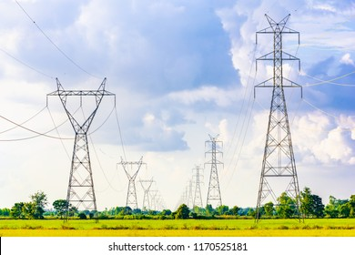 High voltage electrical pole from electricity distribution station at rice field.